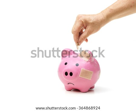 old female hand putting a golden coin into a pink piggy bank with bandage