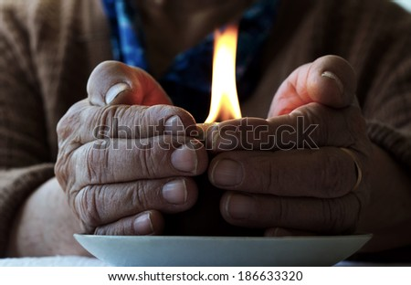 Old female hands with a candle - stock photo