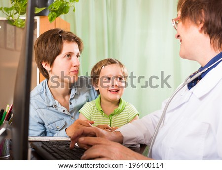 Old female pediatrician doctor examining preschooler at clinic office - stock photo