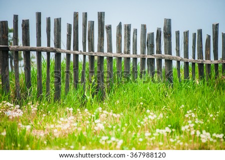Old fence on the green lawn in garden with blue sky as a background - stock photo