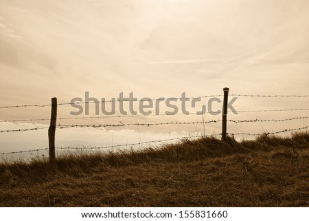 old fence under cloudy sky - stock photo