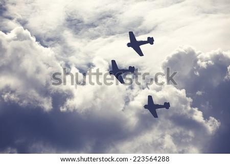 Old fighter planes on bright cloudy sky - stock photo