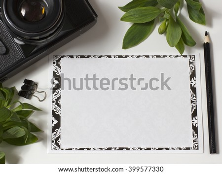 Old film camera, clean sheet of paper and black pencil. It is removed from above. There is a place for the text  - stock photo