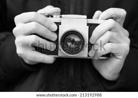 Old film camera in the hands of the photographer. 1940 Retro-Styled Imagery. (Black and White). - stock photo