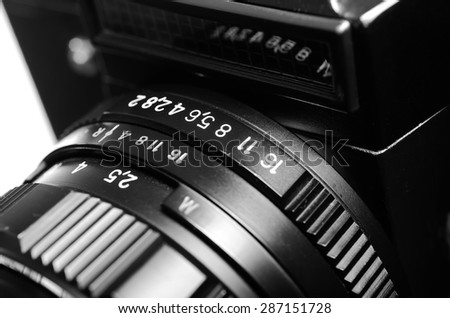 Old film DSLR camera with lens. The scale of the aperture, depth of field and distance. Close up view. Macro. Selective focus. Vintage photo. Black and white. - stock photo