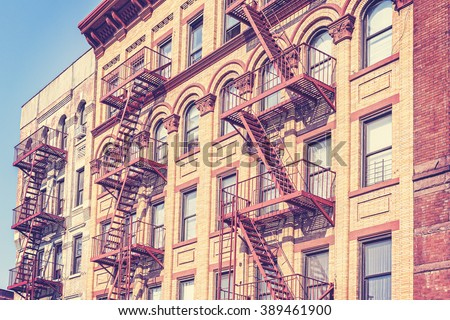 Old film retro toned photo of New York building with fire escape ladders, USA. - stock photo