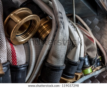 Old fire hoses placed in a compartment of the fire truck - stock photo