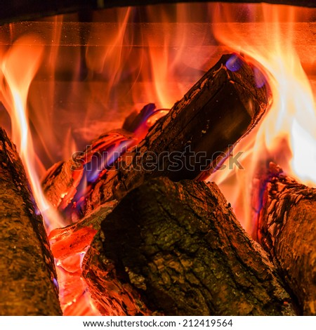 Old fireplace with a burning firewoods - stock photo