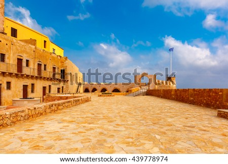 Old Firkas Fortress and The Greek flag in Old harbour of Chania in the morning, Crete, Greece