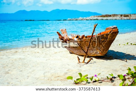 Old fisherman boat with anchor on the sea beach