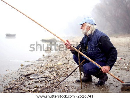 Old fisherman fishing on a river on cloudy day