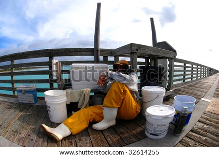 Old fisherman taking a break on pier