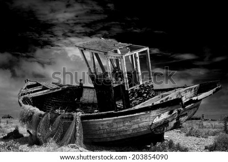 Old fishing boat. An old abandoned fishing boat stranded on a beech in black and white. - stock photo