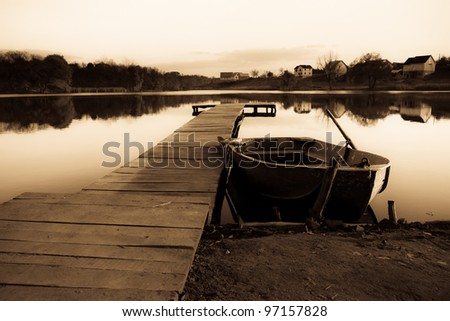 Old fishing boat ashore lake - stock photo