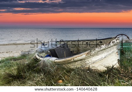 Old fishing boat at dawn, sandy beach of the Baltic Sea, Europe - stock photo