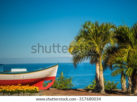Old fishing boat at the Mirador de El Archipenque overlooking the Puerto de Santiago. La Gomera island in the distance. Tenerife, Canary Islands, Spain - stock photo