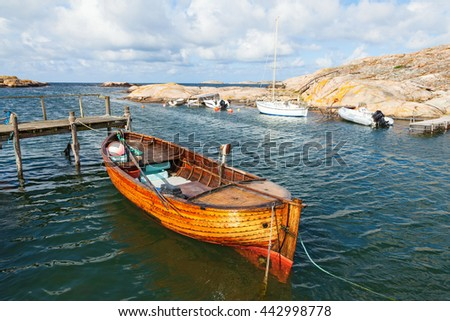 Old fishing boat at the pier on the coast - stock photo