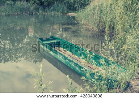 Old fishing boat on a lake shore, vintage - stock photo