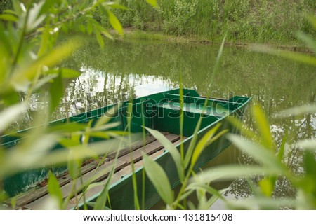 Old fishing boat on a lake shore  with a blurred reeds - stock photo