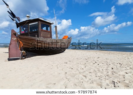Old fishing boat on a sandy beach in sunny day