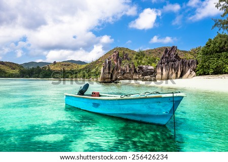 Old fishing boat on a Tropical beach at Curieuse island Seychelles. Horizontal shot - stock photo