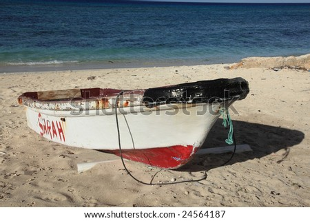 Old fishing boat on clear ocean beach - stock photo
