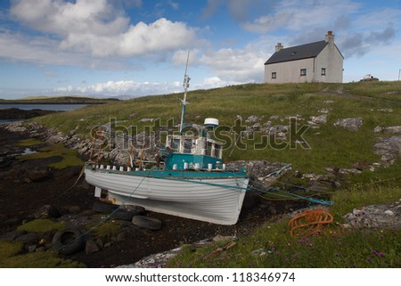 Old fishing boat on the rocks with the tide out on the Isle of Barra in the Outer Hebrides - stock photo