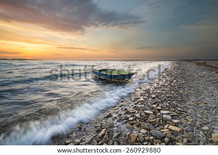 old fishing boat tossed waves of the sea and thrown to the beach - stock photo
