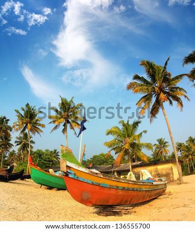 old fishing boats on beach - kerala india - stock photo
