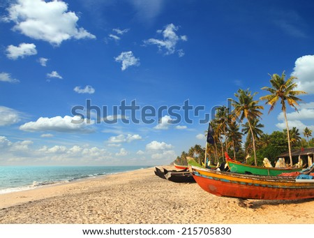 old fishing boats on beach - kerala india - stock photo