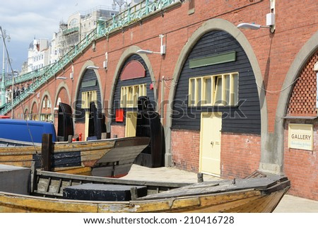 Old fishing boats on the seafront promenade at Brighton in East Sussex. England - stock photo