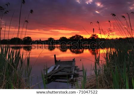 Old fishing bridge on the lake at sunset - stock photo