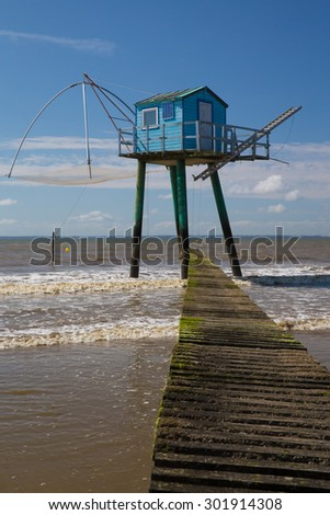 Old fishing hut on piers - stock photo