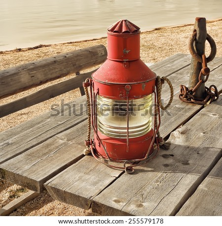 Old fishing lamp on the shore. Vintage effect style pictures - stock photo
