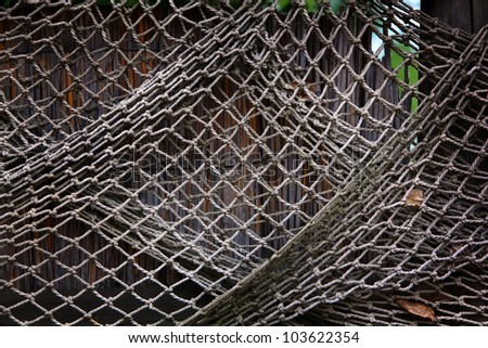 Old fishing net hanging on reed fence - stock photo