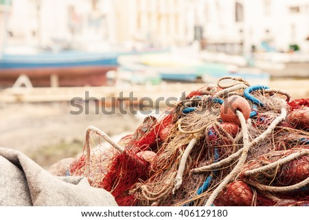 Old fishing net placed on the harbor with blurred boats on background. Photo taken in Sorrento, Italy. - stock photo