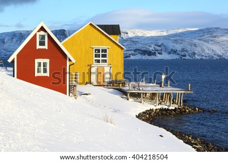 Old fishing pier in northern Norway. A yellow and a red house close to the sea in a norwegian fjord. Varanger peninsula in Finmark County. - stock photo