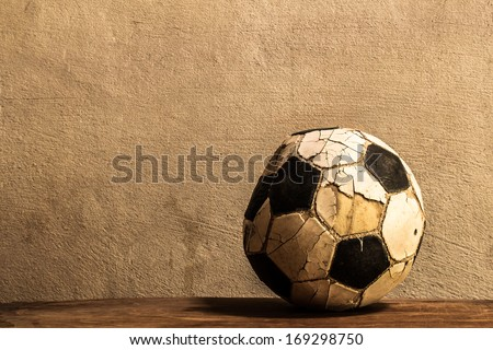 Old football on concrete background - stock photo