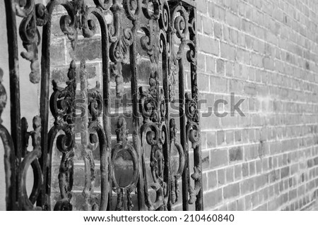 Old forging gate with ornament (entry to abandoned manor) and red stone brick wall. Selective focus on the remote side of the fence. Aged photo. Black and white. - stock photo