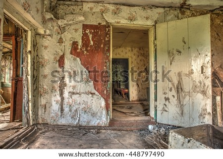 Old forgotten and abandoned home interior in a derelict decaying state with grimy floors and ripped wallpaper. - stock photo