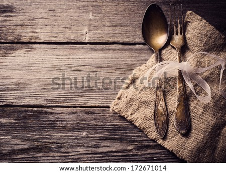 Old fork and spoon on wooden background - stock photo