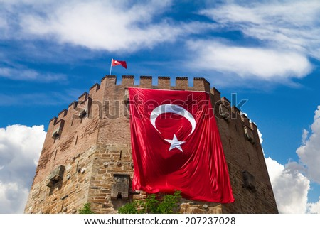 Old fortress, Red Tower, Kizil Kule with wavy Turkish flag in Alanya, Antalya, Turkey - stock photo