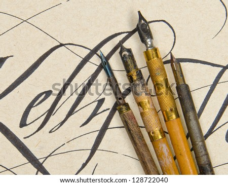 Old fountain pens from the early 1900's on a calligraphy background - stock photo