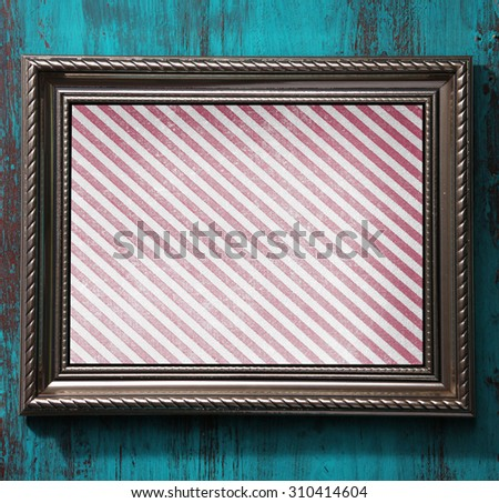 Old frame with striped canvas on wooden background - stock photo