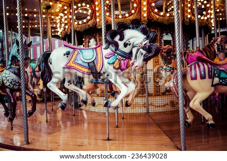 Old French carousel in a holiday park. Three horses and airplane on a traditional fairground vintage carousel. Merry-go-round with horses.  - stock photo