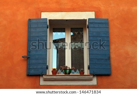 old french open window with blue shutters in red rural house, Provence, France.  - stock photo