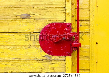 old french train yellow door and part of red door bolt close up as background - stock photo