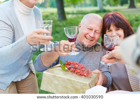 Old friends at birthday party cheering with glass of red wine - stock photo