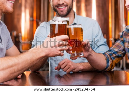 Old friends meeting. Close-up of three happy young men in casual wear toasting with beer while sitting in beer pub together - stock photo