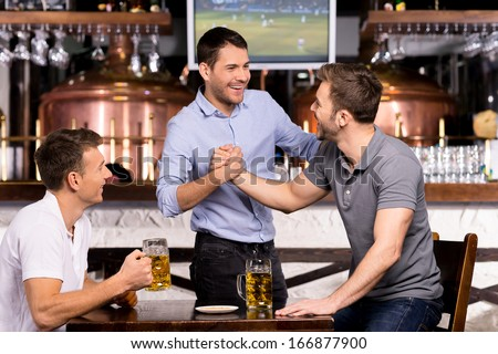 Old friends meeting. Three cheerful friends meet each other in beer pub - stock photo